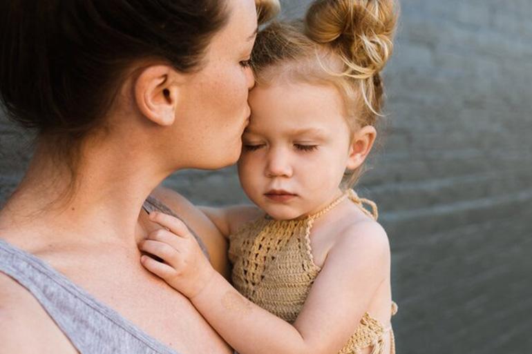 майка целува дъщеря си