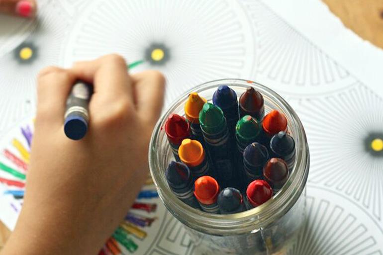 дете което оцветява книжка